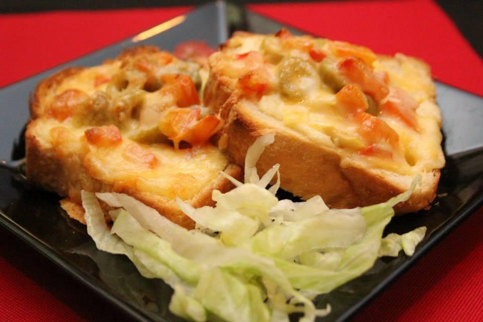 Sanduíche gratinado de champignon, azeitonas e tomate, ao molho de quatro queijos