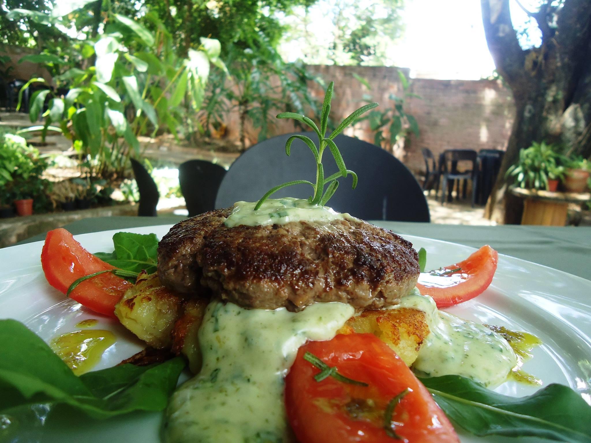 Hambúrguer, batata ao murro ou mousseline de mandioquinha, requeijão com ervas frescas, rúcula e pétalas de tomate